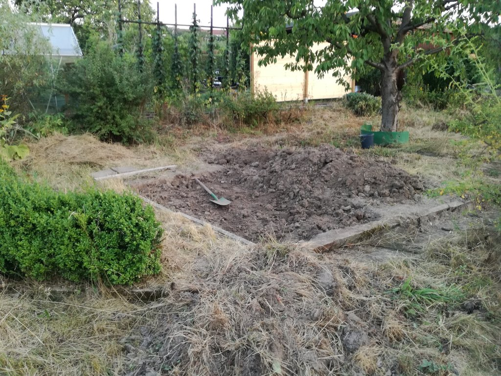 Ein teilweise vorbereitetes Gemüsebeet, trockene Erde, ein Haufen Erdklumpen